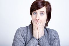 Shocked girl covers mouth with hands Royalty Free Stock Photography