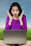 Shocked girl with laptop at field Stock Photos