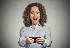 Shocked girl looking at phone bad news wow face expression Stock Image