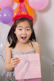 Shocked girl opening gift box at her birthday party Royalty Free Stock Photos