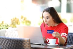 Shocked girl paying online with credit card and laptop royalty free stock photo