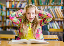 Shocked girl reading a book in the library Stock Photos