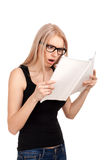 Shocked girl reading womens magazine Stock Images