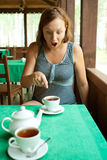 Shocked girl sees something in cup of tea Stock Image