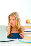 Shocked girl sitting at desk and looking on laptop Royalty Free Stock Photo