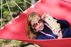 Shocked girl staring at the camera. Shocked girl staring at camera In Hammock. Young woman in glasses on red hammock taking pictures with cell phone, smartphone Stock Photography