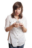 Shocked girl staring at smartphone Royalty Free Stock Photos