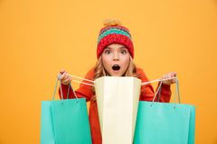 Shocked girl in sweater and hat holding and opening packages. Shocked Young girl in sweater and hat holding and opening packages while looking at the camera over royalty free stock images