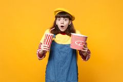 Shocked girl teenager in french beret, denim sundress hold plastic cup of cola or soda, bucket of popcorn isolated on. Yellow background. People sincere stock image