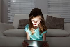 Shocked girl using digital tablet Royalty Free Stock Photos