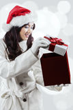 Shocked girl in winter clothes opening a gift Royalty Free Stock Photography