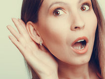 Shocked gossip girl eavesdropping with hand to ear. royalty free stock image