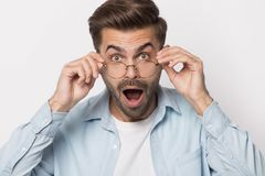 Shocked guy lowering glasses looking at camera studio shot. Shocked guy wearing glasses open mouth isolated on white, millennial man lowering spectacles looking stock image