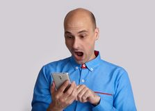 Shocked guy reading Message on his smartphone royalty free stock images