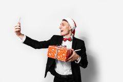 Shocked guy in a suit and a santa hat, in his hands - a Christmas gift, he takes pictures of himself on a smartphone. On a white background royalty free stock images
