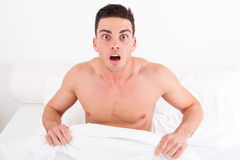 Shocked half naked young man in bed  looking down at his underwe Royalty Free Stock Images