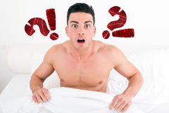 Shocked half naked young man in bed  looking down at his underwear Royalty Free Stock Photo
