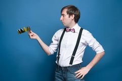 Shocked handsome man in shirt, suspender, bow tie with hand on hip, holding and looking at golden crown royalty free stock photos