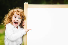 Shocked and happy child with school blackboard.