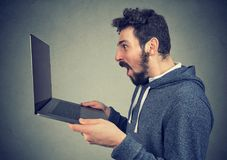 Shocked happy man watching new laptop stock photography