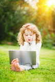 Shocked and happy surprised child with laptop sitting on the gra Stock Images