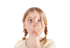 Shocked by a hearing aid. Cute girl looking at a hearing aid with wide eyes stock image