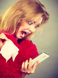Shocked heartbroken woman looking at her phone. Betrayal, bad relationship, hurt love concept. Shocked heartbroken woman crying and looking at her phone Stock Image