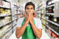Supermarket employee covering mouth as secret concept. Shocked indian male supermarket employee covering mouth with palms as not-telling secret concept stock photography