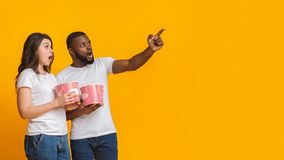 Shocked interracial couple holding popcorn and pointing aside at copy space