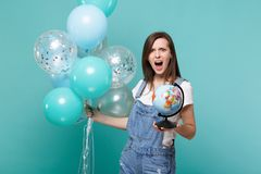 Shocked irritated screaming young woman holding Earth world globe, celebrating with colorful air balloons isolated on stock photo