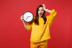 Shocked irritated woman in yellow fur sweater putting hand on head, holding round clock isolated on red background. Time. Is running out. People sincere stock photography