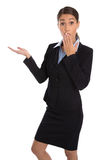 Shocked isolated businesswoman in suit presenting over white. Stock Photo