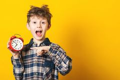 Shocked kid boy holding clock alarm, copy space. Kid isolated over yellow background. Time for school. Little student overslept. T. Ime concept. Excited boy at stock photos