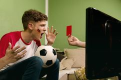Shocked kid, red card in soccer game on TV stock photos