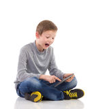 Shocked kid with tablet. Stock Photos