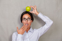 Shocked lady with apple on head and open mouth Stock Images