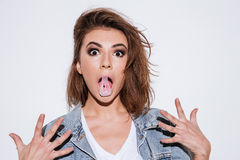 Shocked lady with bubble gum. Picture of a young shocked lady dressed in jeans jacket standing isolated over white background with bubble gum stock photos
