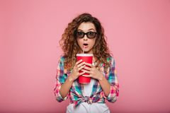 Shocked lady with cola and popcorn wearing 3d glasses. Surprised caucasian woman in 3d glasses holding cola and looking camera isolated over pink Stock Photos
