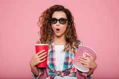 Shocked lady with cola and popcorn wearing 3d glasses. Surprised caucasian woman in 3d glasses holding cola and popcorn and looking camera isolated over pink Stock Photos