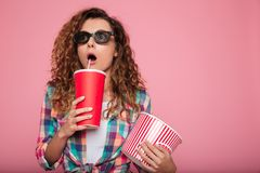 Shocked lady with cola and popcorn wearing 3d glasses. Surprised caucasian woman in 3d glasses holding cola and popcorn and looking camera isolated over pink Royalty Free Stock Photos