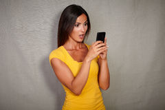 Shocked lady texting while using smart phone Stock Photos