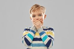 Shocked little boy closing his mouth by hands royalty free stock photos