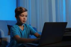 Shocked little child with laptop. Danger of internet. Shocked little child with laptop in dark room. Danger of internet stock image