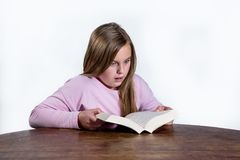 Shocked little girl with a book on a white background. Shocked little girl at the desk with a book learning on a white background Stock Images