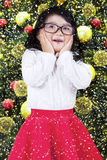 Shocked little girl with christmas decoration Royalty Free Stock Photos