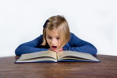 Shocked little girl with a book on a white background. Shocked little girl at the desk with a book learning on a white background Stock Photography