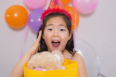 Shocked little girl with gift at her birthday party Stock Images