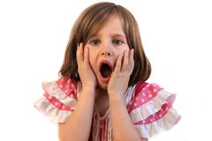 Shocked little girl. Little girl holds hands to face with open mouthed expression of shock Stock Photo
