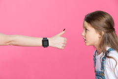 Shocked little girl looking at woman with smartwatch showing thumb up Royalty Free Stock Photo