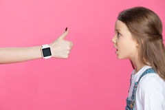 Shocked little girl looking at woman with smartwatch showing thumb up Royalty Free Stock Image